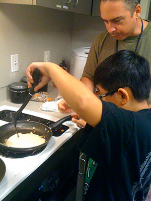 student cooking pancakes on stovetop