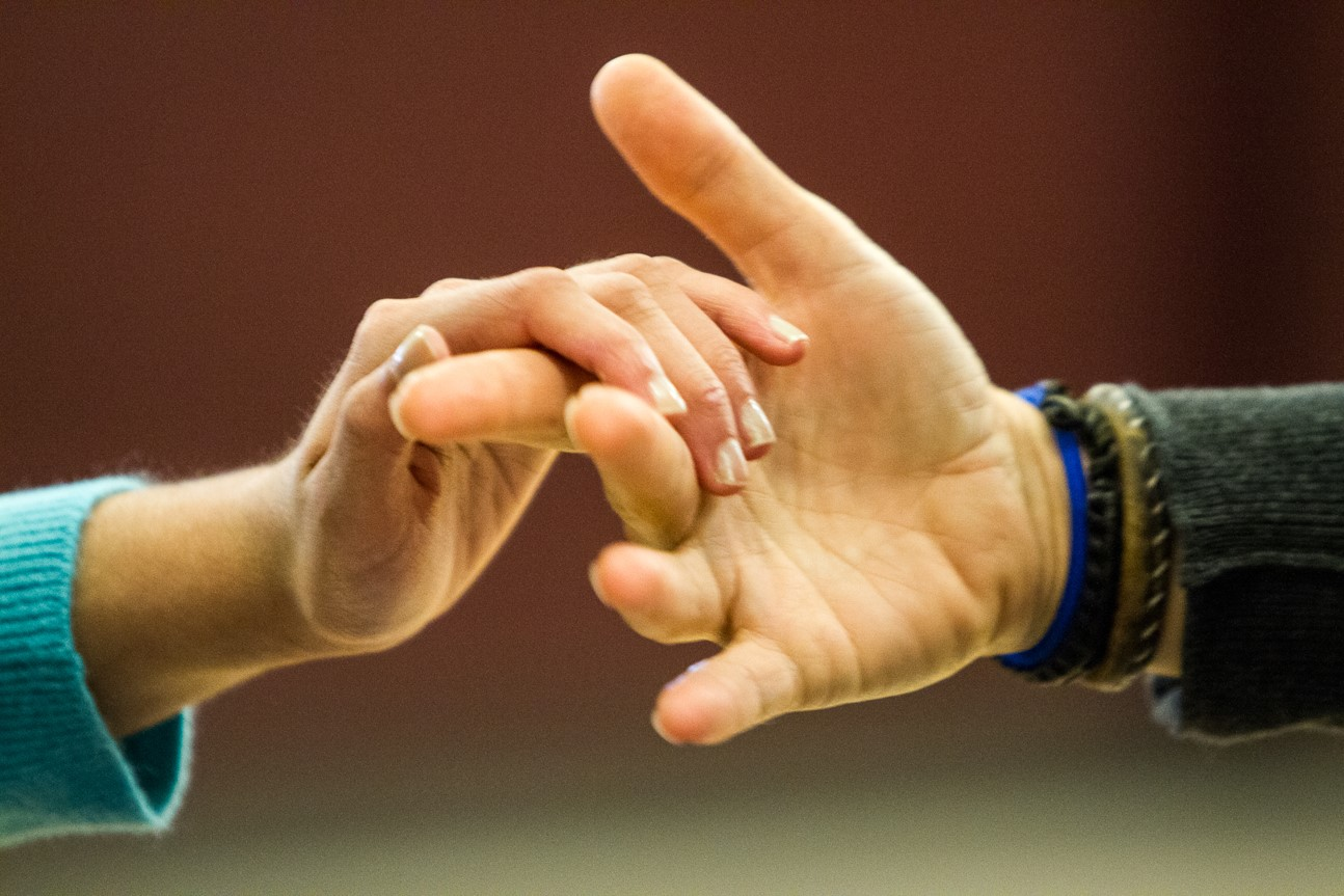 The hands of the child who is deafblind reaches out to connect to the adult's hand.