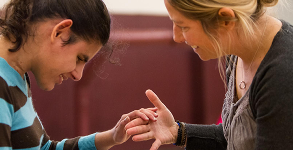 A teacher invites a young deafblind girl to join her by offering her hand under the girls hand.