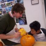 A teacher of students who are deafblind pulls the top out of a pumpkin he is carving with his student while the student looks on.