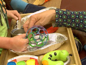 A child and an adult explore objects together tactually.