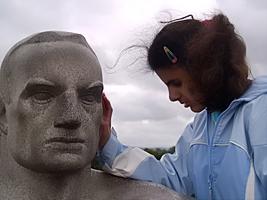 Girl examining statue