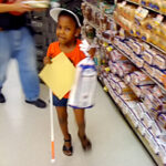 A young girl carrying a loaf of bread uses her travel cane to navigate the grocery store.