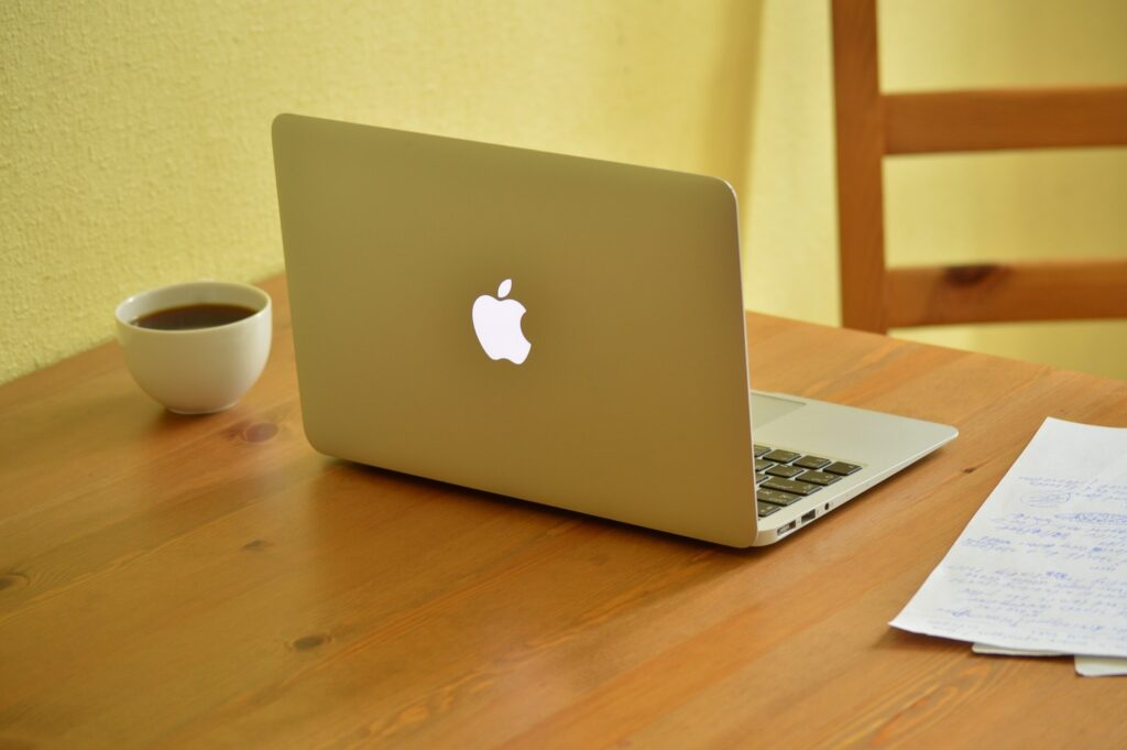 Apple laptop open on table with a cup of coffee next to it