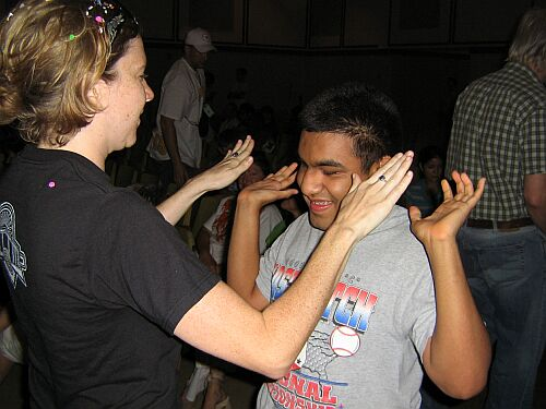 A young man who is deafblind interacts with his teacher by playing a clapping game together.