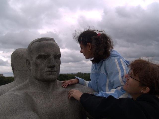 A mother and her daughter who is deafblind tactually explore a large sculpture of a man. It is outdoors and storm clouds can be seen behind. The wind blows their hair.