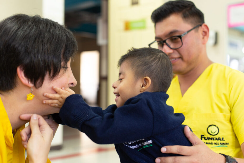 A small child touches the face of his mom while dad looks on.