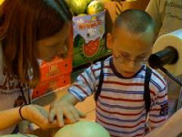 Young boy and his intervener share the experience of tactually exploring a melon.