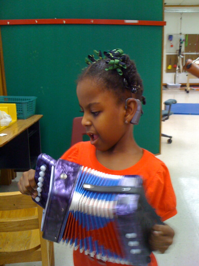 A young girl who is deafblind plays with an accordion.