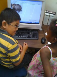 A young boy and a young girl who are deafblind look at the image of a bear on a computer and have a conversation.