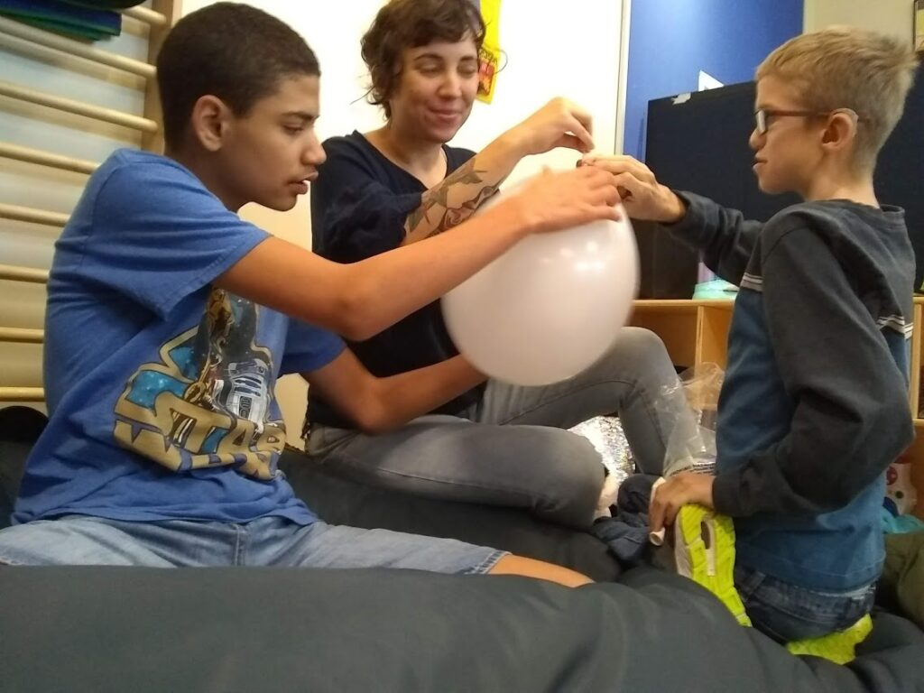 Deafblind students and their TDB interact with a balloon