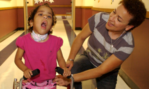 Young preschool girl learning to use a walker.