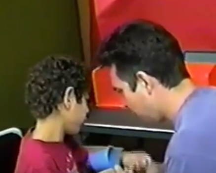 Young boy who is deafblind and his teacher having a conversation.