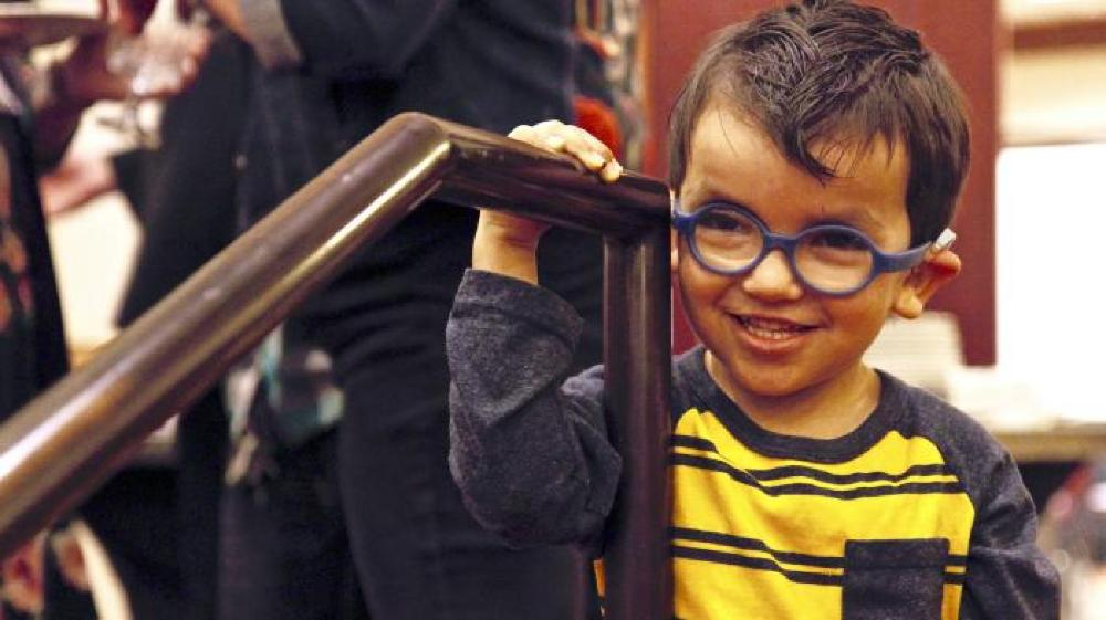 A young toddler who is deafblind grasps the handrail to support him as he prepares to go down the steps.