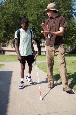 An orientation and mobility instructor works with a young man who is deafblind and using a travel cane.
