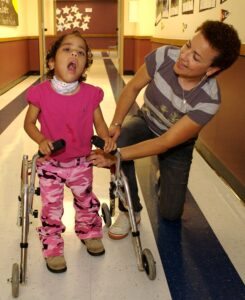 An O&M Specialists works with a child who is learning to use a walker.