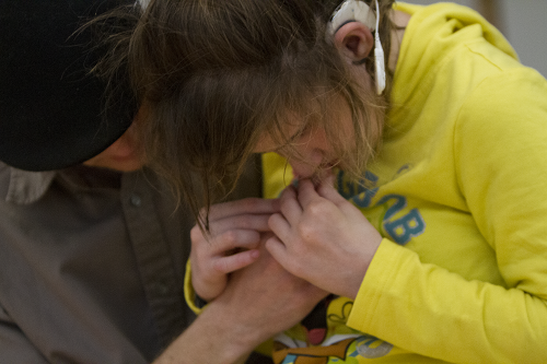An adult comforts a child during an interaction.