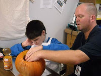 A young man places his hand over his teachers hand as they explore the inside of a pumpkin.