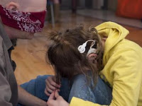 A young girl who is deafblind hugs her knees to her chest and buries her head; these are behaviors that many indicate she is experiencing distress.