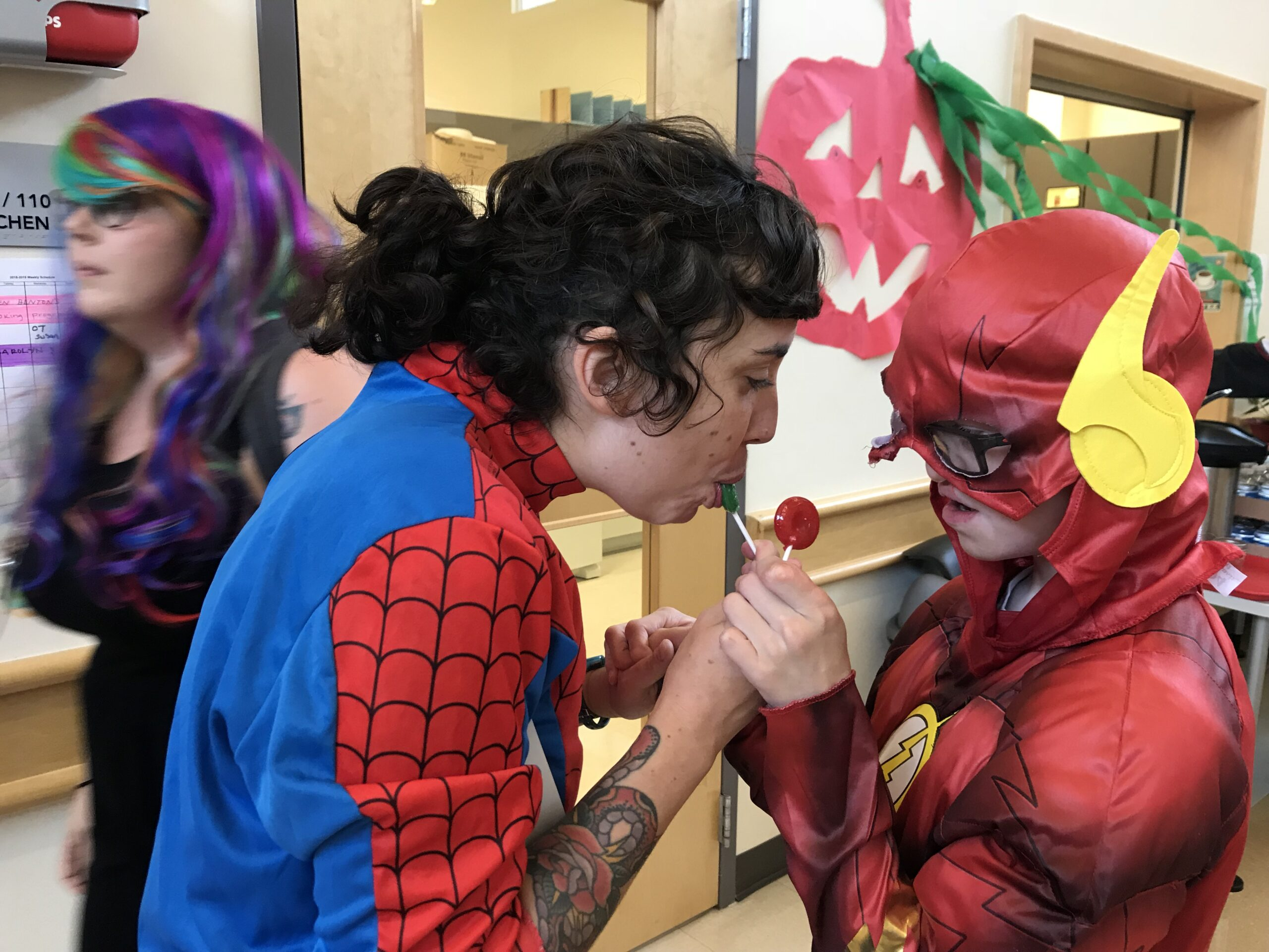 A teacher and young boy dressed in Halloween costumes share the experience of eating lollipops.