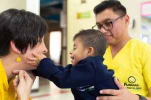 A young toddler who is deafblind reaches out to touch his mom's face while dad holds him.