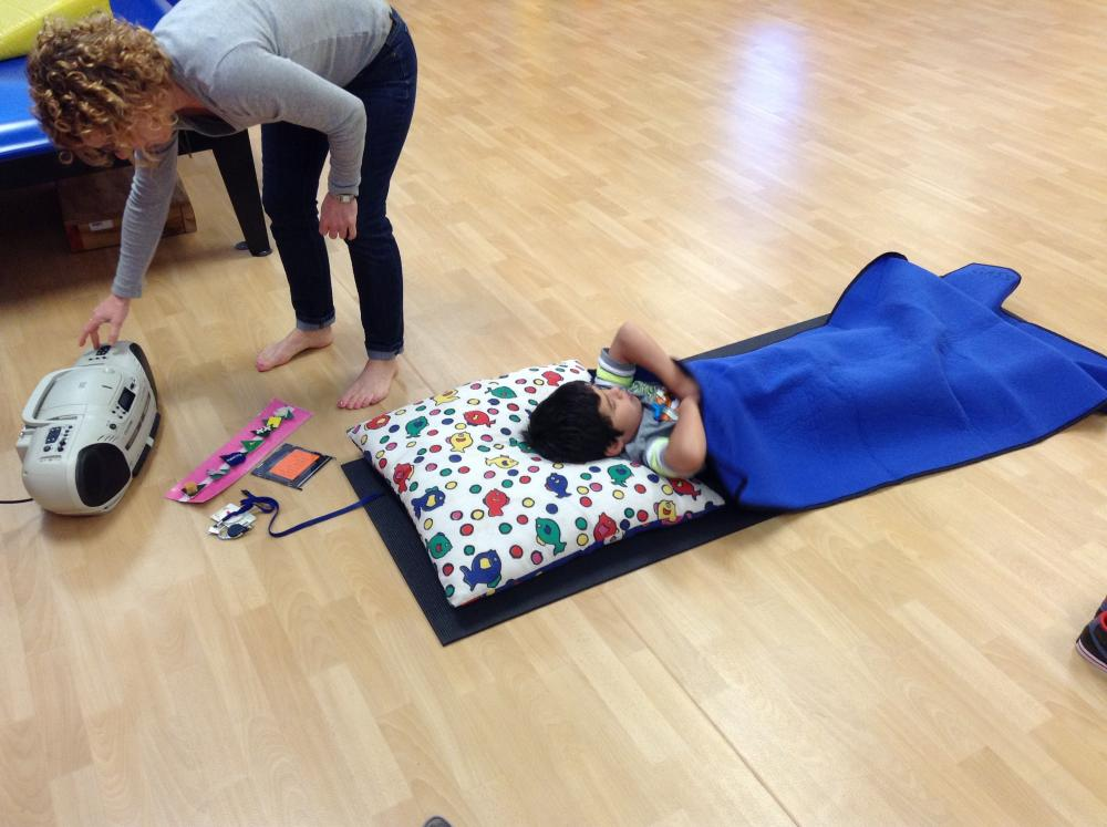 A teacher helps a child learn to calm and relax during a yoga class.