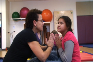 A young girl is learning yoga from her teacher which helps her relax when she is stressed.