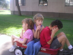 Three young children who are deafblind sit close together in a red wagon.