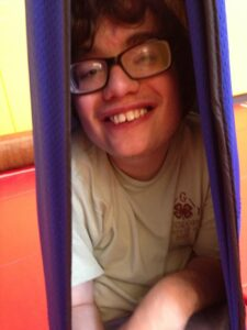 A young man takes comfort in being nestled tightly in a cloth swing.